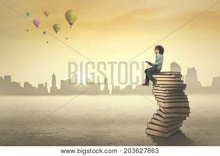 Image of African male college student sitting on a stack of book while looking at air balloons in the sky