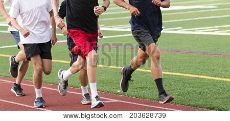 Five high school boys running fast in a group on a track during cross country practice.