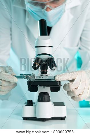 Research scientist working with specimen plate on microscope with molecule model over blue lab background with selective focus
