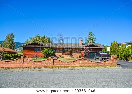 Red brick residential house with red brick wall on front yard. Family house with black truck parked on asphalt driveway