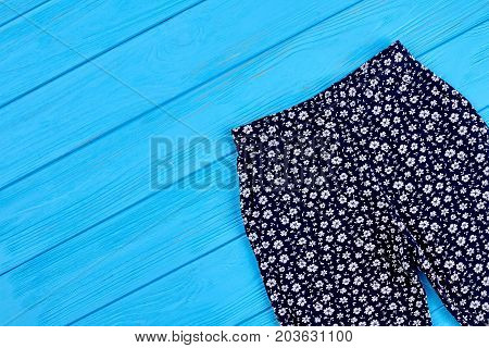 Baby girls pants, copy space. Top view of kids summer trousers on wooden background.