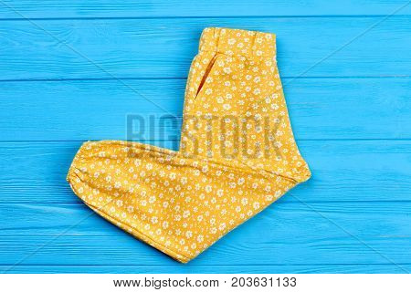 New folded trousers for baby girl. Top view of yellow infant girl trousers on blue wooden background. Kids fashion outfit.