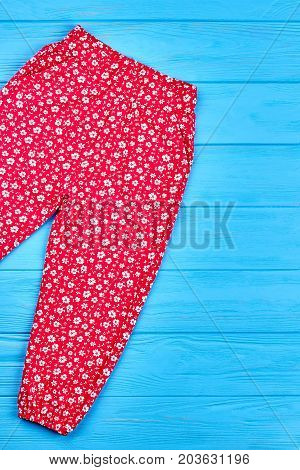Fashionable summer baby girl pants. Vertical image of kids girl red patterned trousers lying on blue wooden background.