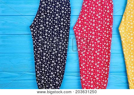 Three pairs of colorful pants close up. Summer cotton colorful trousers in vintage print lying on blue wooden background. Modern clothing for children on sale.