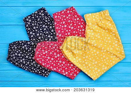 New organic folded baby pants. Close up of colorful cotton summer trousers for little girls, top view. Modern childs clothing on sale.