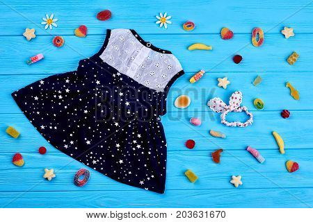 Stylish high quality children clothing. Cute baby-girl summer blue and white dress, hairband, sweets. Kids summer fashion background.