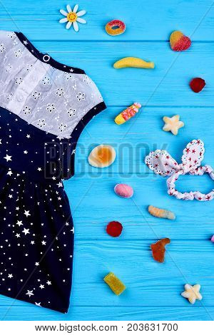 Baby-girl summer clothing, accessories. Patterned cotton dress, hairband, sweets. Little girl summer fashion background.