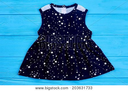 Sleeveless baby-girl cotton dress. Textile sundress for little gils on blue wooden background. Casual kids clothing.
