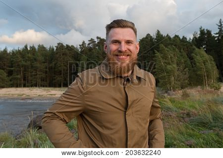 Portrait of a smiling red-haired bearded man in the nature