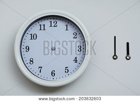 A clockface and an hour hand and the long hand of the wall clock