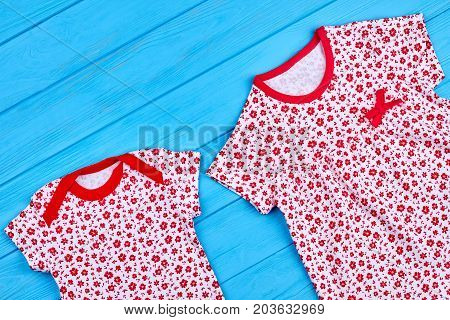 Flower print baby bodysuit and dress. White clothes in red floral ptint for toddler girl on blue wooden background. Baby clothes on sale.
