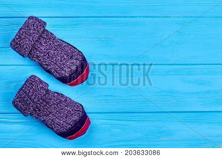 Childs wool socks, copy space. Kids purple woolen knitted socks on blue wooden background. Natural knitted woolen socks for children. Room slippers with leather soles.