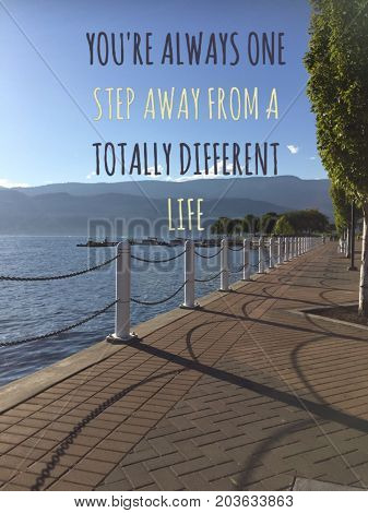 Inspirational motivational text on scenic lake view with brick walkway along lake shore. Conceptual image with words: You're always one step away from a totally different life.