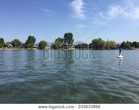 Beach And Houses Along Lake Shore In Background Of Lake Landscape With Buoy