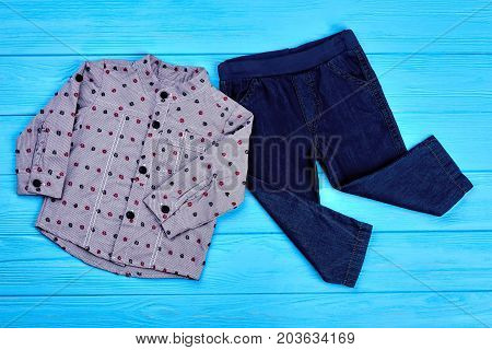 Baby-boy modern denim apparel. Toddler boy fashion design jeans and shirt on blue wooden background, top view. New collection of trendy garment for little boys.