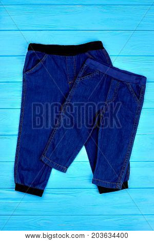 Jean pants for babies, top view. Childs trendy dark blue jean trousers on blue wooden background. Toddlers brand jeans on sale.