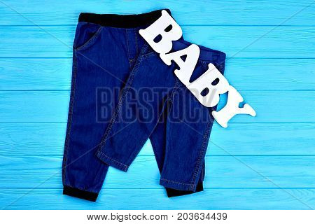 Infant kids dark jean trousers. Baby boys and girls jean pants on sale. Kids denim trousers background.