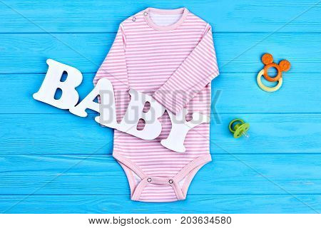 High quality natural bodysuit for baby-girl. Infant baby striped cotton bodysuit, accessories, blue wooden background. Infant baby clothes and accessories background.