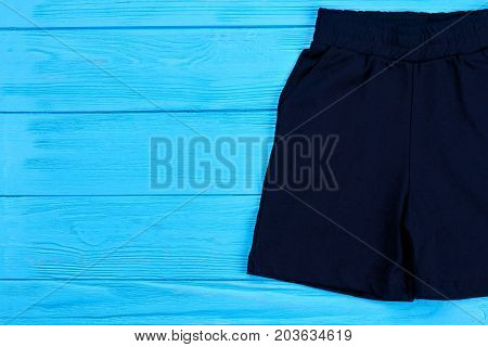 Kids dark cotton shorts and copy space. Toddler boy textile short pants on blue wooden background. Childs cotton summer garment.