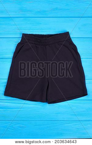Toddler boys shorts for casual wear. Top view of black textile shorts for little boys, blue wooden background. Kids cotton clothes on sale.