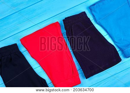 Kids colored shorts background. Setting of different shorts for boys on wooden background. Toddlers summer clothing.