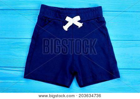 Cotton shorts for toddler boy. Textile blue short pants for infant boy on wooden background. Childrens apparel on sale.