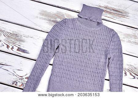 Boys turtleneck warm gray sweater. Male gray knitted winter jumper on vintage white background. Children winter knitwear.