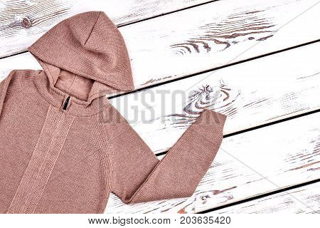 New brown hooded sweater. Children cotton cardigan with hoodie, old wooden background. Top quality of knit jacket for boys.