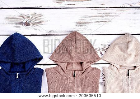 Hooded knitted pullovers, copy space. Beautiful set of new knitted hooded sweaters for children, top view. Brand knit jackets.