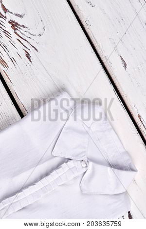White female shirt, top view. Girls white cotton blouse folded on old wooden background. High quality fabric white woman blouse.