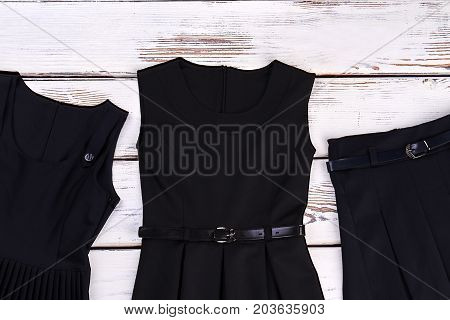 Set of black garment for school girls. Classic black dresses and belted pleated skirt for school wear. Girls school classic clothes.