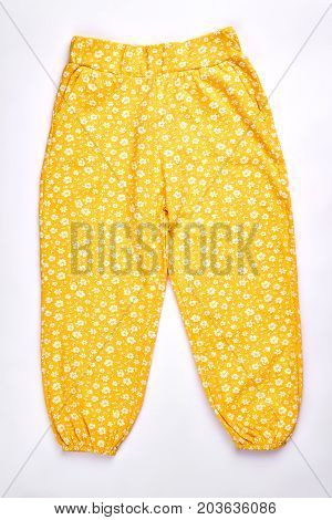Baby-girl yellow patterned harems. Toddler girl cute design cotton pants isolated over white. Infant girls casual summer harems.