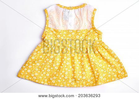 Baby-girl yellow patterned dress. Newborn baby-girl natural cotton printed dress with embroidery, white background. Infant girl sundress for casual wear.