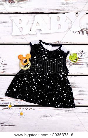 Baby-girl black cotton summer dress. Toddler girl cute cotton top, pacifier, teether, old wooden background, top view.