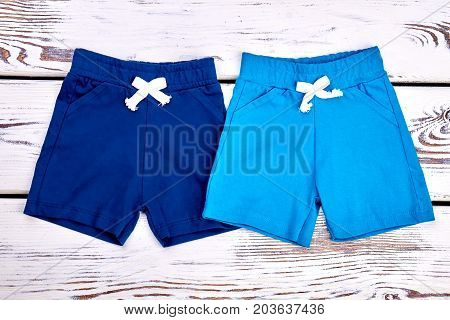 Collection of new shorts for baby boys. Toddler boy set of colored shorts on old wooden background. Kids new casual shorts.