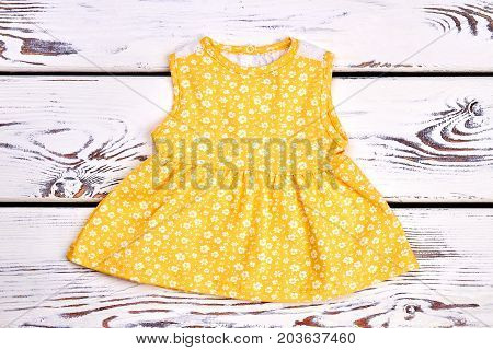 Baby-girl cute yellow cotton dress. Toddler girl sleeveless patterned top on white wooden background.