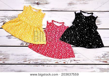 Set of beautiful dresses for newborn girls. Collection of new printed tops for infant girls, top view.