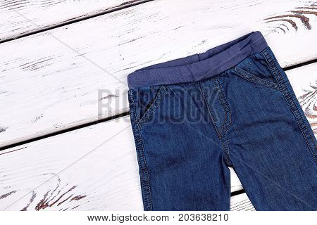 Kids denim pants, top view. Childs jeans on white wooden background. High quality kids apparel.