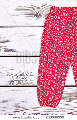 Infant girl flowers print trousers. Baby girl high quality patterned trousers, old wooden background. Infant girl fabric long pants on sale.