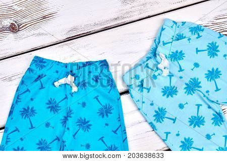 High quality kids summer trousers. Baby boys and girls blue patterned leggings on wooden background. Toddler kids summer garment.
