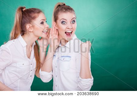 Young woman telling her friend some secrets two women talking gossiping. Excited emotional girl whispering to human ear