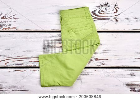 Baby-girl new brand trousers. Infant girl modern pants folded on white wooden background, top view. Kids fashion garment.