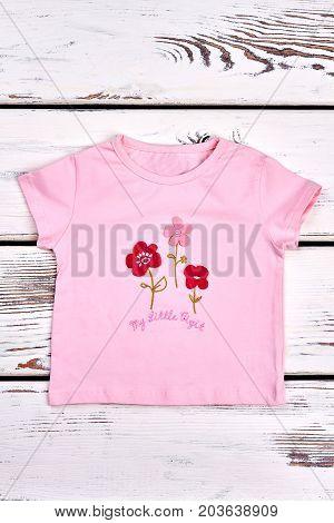 Baby-girl short sleeve t-shirt. Infant girl pink flowers cartoon t-shirt, white wooden background. Kids casual garment.