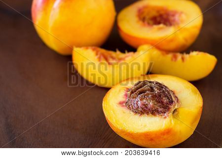 Ripe juicy Nectarines organic fruits whole and slice on wooden background. Selective focus. Toned photo.