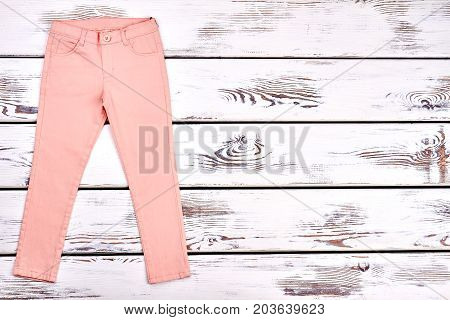 Teen girls modern summer trousers. Female slim peach color pants on white wooden background, copy space. Woman summer fashion outfit.