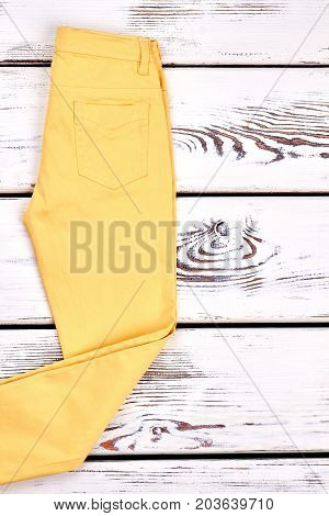 Womans yellow casual pants. Cotton solid yellow trousers on white wooden background. Girs new summer pants on sale.