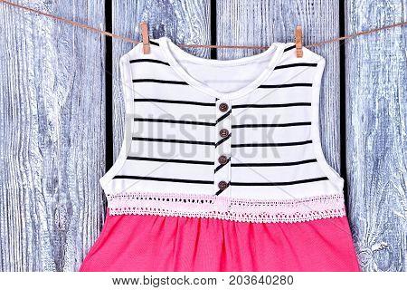 Baby dress hanging on clothesline. Infant girl elegant dress drying on rope, grey wooden background.
