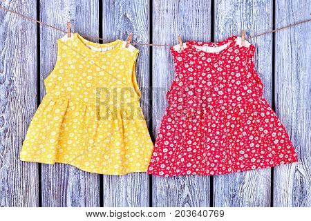 Kids dresses hanging on rope. Baby-girl apparel drying on clothesline, old wooden background.
