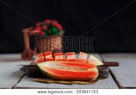Papaya is half and cut on old wooden floor.