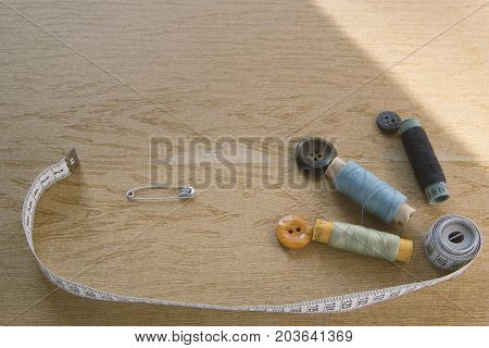 Sewing still life - multicolored cotton thread spools, thimble, needle, measuring tape, top view